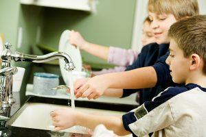 bambini che lavano i piatti